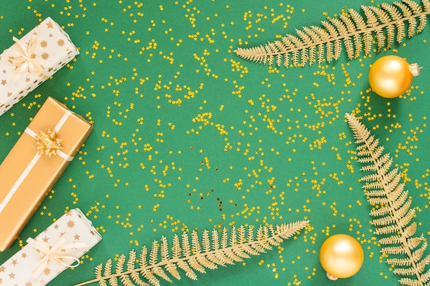 Festlicher hintergrund mit dekorationen, hell glänzenden goldenen farnblättern und geschenkboxen mit weihnachtskugeln auf grünem hintergrund mit glitzernden goldenen sternen, flache lage, draufsicht, kopierraum