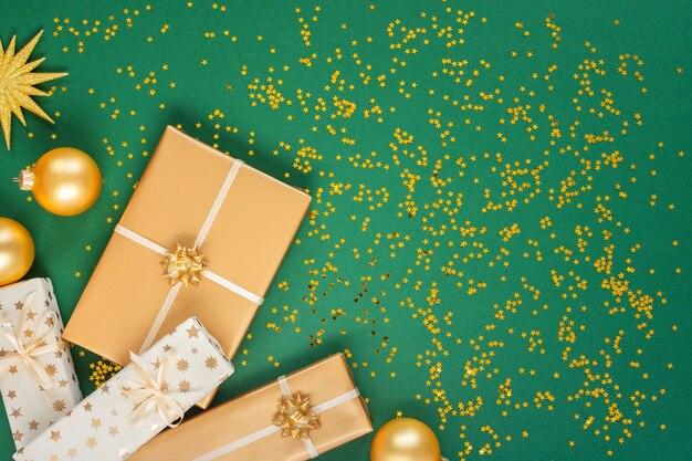 Festlicher hintergrund mit dekorationen, hellem goldstern und geschenkboxen und weihnachtskugeln auf grünem hintergrund mit goldenen glitzersternen, flacher lage, draufsicht, kopierraum