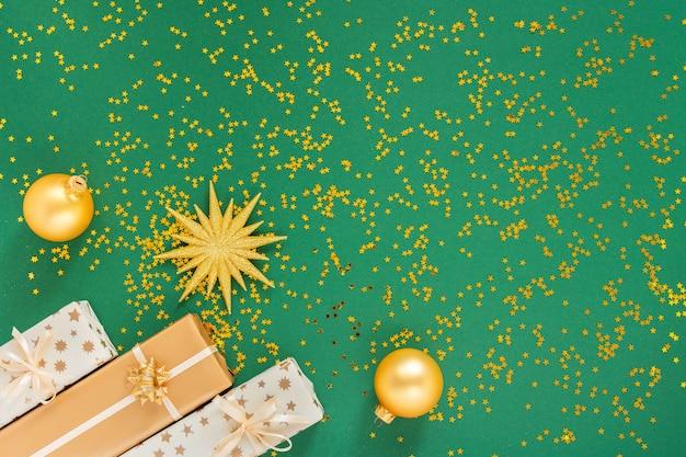 Festlicher hintergrund mit dekorationen, leuchtend goldenem stern und geschenkboxen und weihnachtskugeln auf grünem hintergrund mit glitzernden goldenen sternen, flache lage, draufsicht, kopienraum