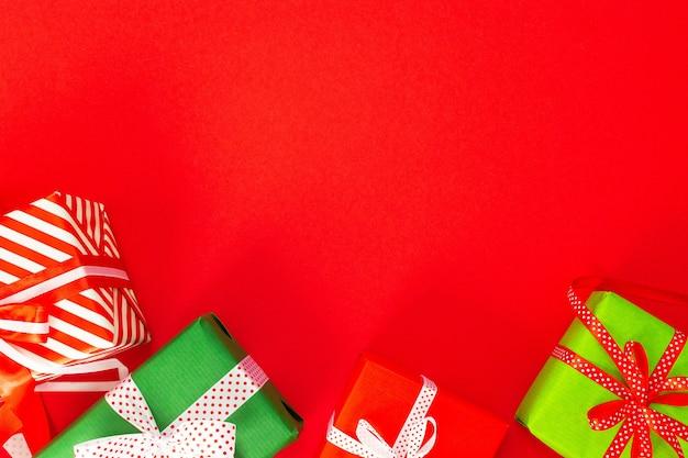 Festlicher hintergrund mit farbigen geschenken, geschenkboxen mit band und schleife auf rotem hintergrund, flache lage, draufsicht, leerer raum für text