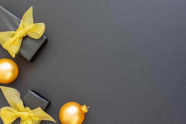 Festlicher hintergrund mit golddekorationen, geschenkboxen mit glänzendem goldenem band und weihnachtskugeln auf schwarzem hintergrund, flache lage, draufsicht, kopierraum