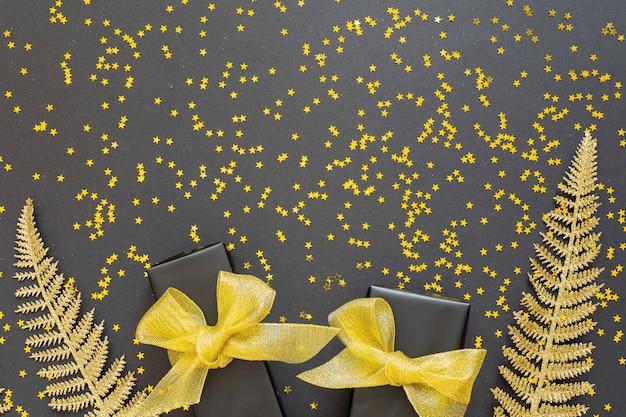 Festlicher hintergrund mit goldenen dekorationen, glänzenden goldenen farnblättern und geschenkboxen auf schwarzem hintergrund mit goldenen glitzersternen, flacher lage, draufsicht, kopierraum