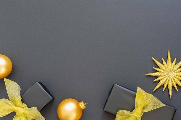 Festlicher hintergrund mit goldenen dekorationen, glänzenden goldenen sternen und geschenkboxen und weihnachtskugeln auf schwarzem hintergrund, flache lage, draufsicht, kopierraum