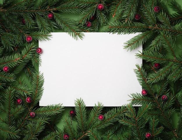 Festlicher hintergrund mit kopienraum für text. weihnachtsgrenze von tannenzweigen und stechpalmenbeeren. flache lage, ansicht von oben