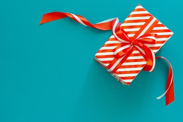 Festlicher hintergrund mit rotem und weiß gestreiftem geschenk, geschenkbox mit band und schleife auf einem blauen türkisfarbenen hintergrund, flache lage, draufsicht