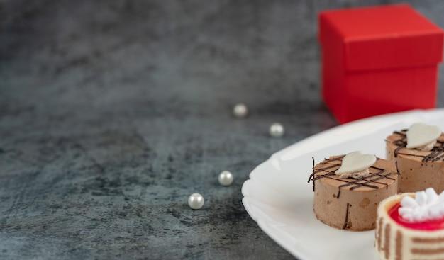 Festlicher hintergrund mit roter geschenkbox, weißen perlen und minikuchen