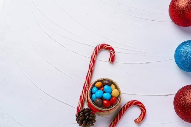 Festlicher hintergrund mit zuckerstangen und weihnachtskugeln auf holzbrett