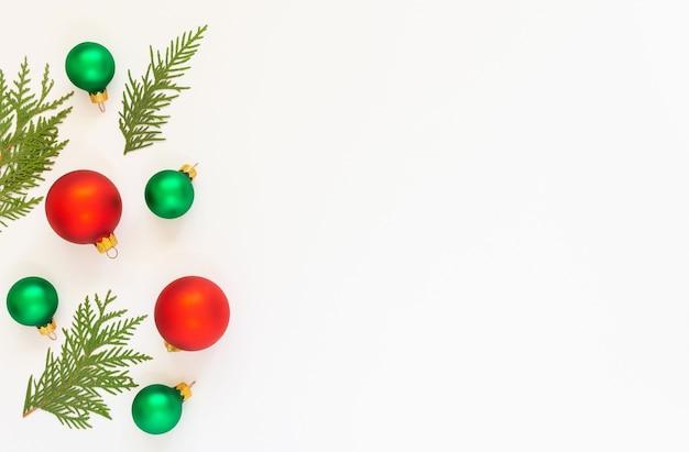 Festlicher hintergrund, rote und grüne christbaumkugeln mit tannenzweigen auf weißem hintergrund, flache lage, draufsicht, kopienraum