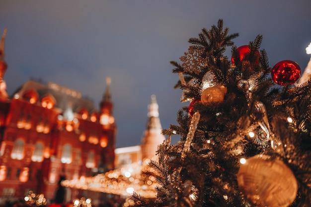 Festlicher hintergrund schöne goldene bokeh-lichter gegen die nachtstadt-weihnachtsbaumzweige