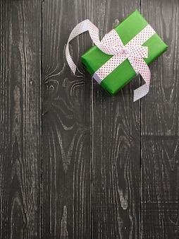 Festlicher hintergrund, vertikales banner mit grüner geschenkbox und band auf einem braunen hölzernen hintergrund, valentinstag oder geburtstag, weihnachten