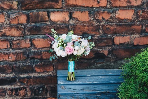 Festlicher hochzeitsblumenstrauß gebunden mit band, steht auf holzbank gegen ruinierte backsteinmauer