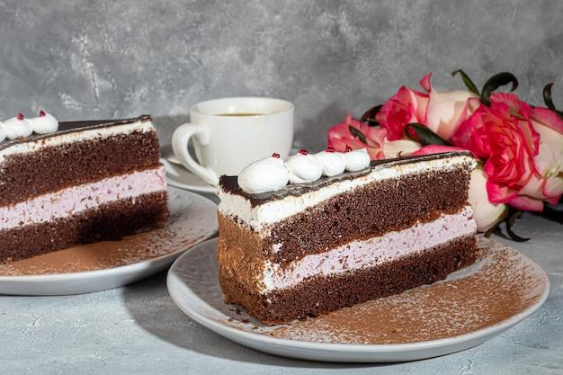Festlicher kuchen mit schokolade und knuspriger zwischenschicht. zwei portionen. auf grauem hintergrund. geburtstag, feiertage, süßigkeiten. speicherplatz kopieren.
