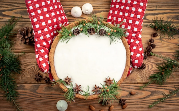 Festlicher kuchen mit weißer creme, verziert mit zapfen, nadelzweigen und sternanis. konzept des neuen jahres und weihnachten. kopieren sie platz und draufsicht.
