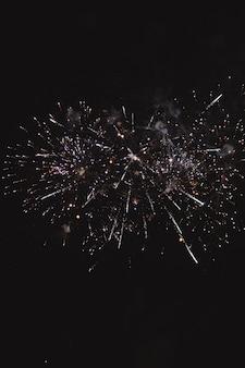 Festlicher mehrfarbiger gruß auf dem hintergrund des dunklen nachthimmels. gruß von der pyrotechnik.