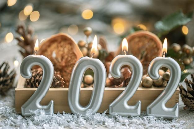 Festlicher neujahrshintergrund mit kerzen in form der zahlen 2022.