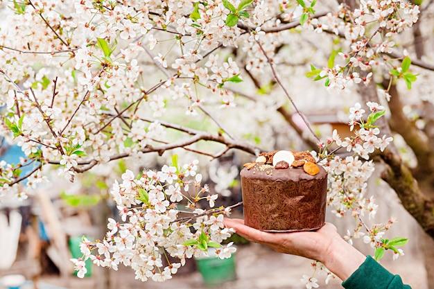 Festlicher osterkuchen auf dem hintergrund der blühenden kirschen im garten.