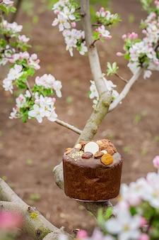 Festlicher osterkuchen auf dem hintergrund eines blühenden apfelbaums im garten.