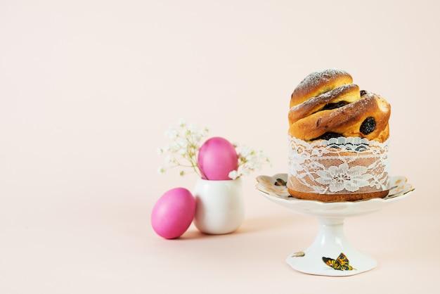 Festlicher osterkuchen mit rosinen und bemalten rosa eiern, verziert mit frühlingsweißen blumen.
