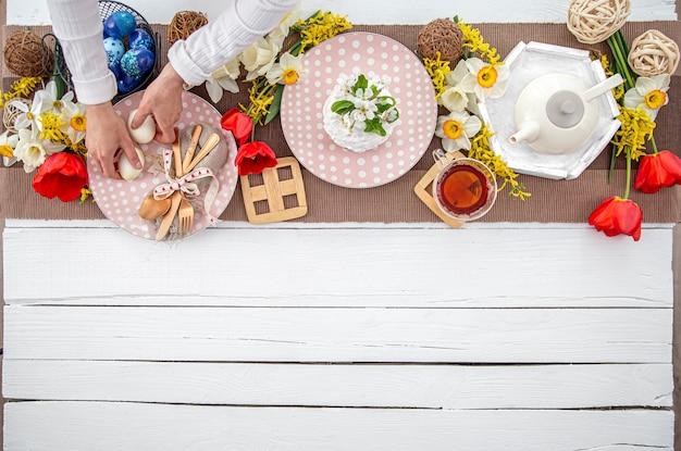 Festlicher ostertisch mit hausgemachtem osterkuchen, tee, blumen und dekordetails kopieren platz. familienfeier-konzept.