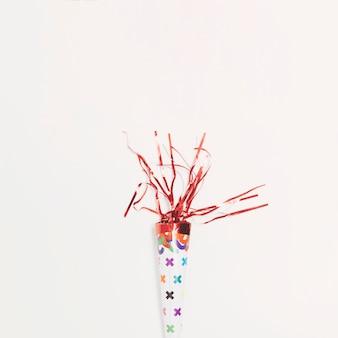 Festlicher parteipopper mit rotem serpentin gegen weißen hintergrund