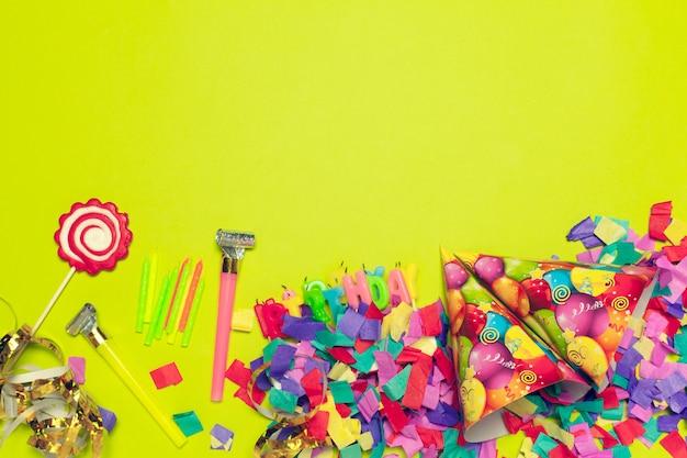 Festlicher partydekor und konfettis auf farbigem hintergrund