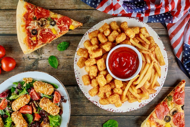 Festlicher partytisch mit gebratener kartoffel, pizza und gemüse für amerikanischen feiertag.