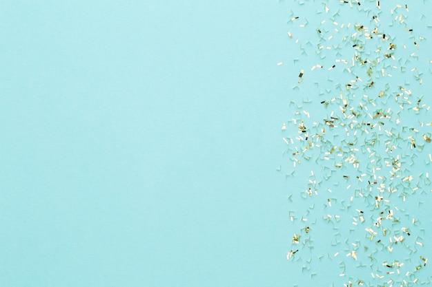 Festlicher pastellhintergrund. weihnachtssterne und leuchtender glitzer, konfetti auf pastellfarbenem hintergrund. weihnachten. hochzeit. geburtstag. valentinstag. flach liegen.