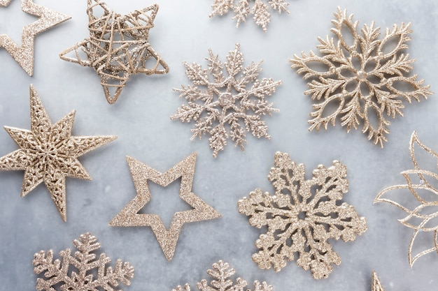 Festlicher pastellhintergrund. weihnachtssterne und leuchtender glitzer, konfetti auf pastellfarbenem hintergrund. weihnachtshintergrund, flache lage.