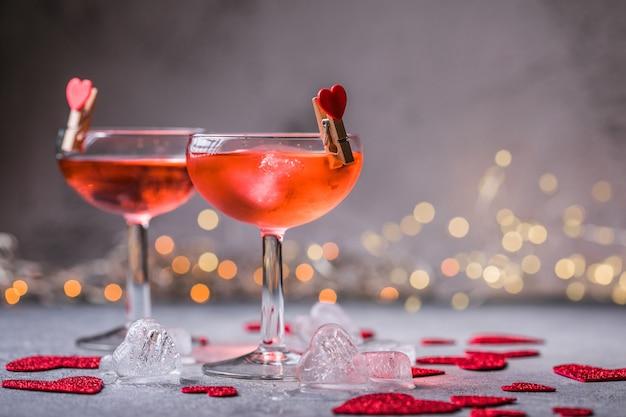 Festlicher rosa cocktail mit champagner oder prosecco zum valentinstag. ein paar gläser