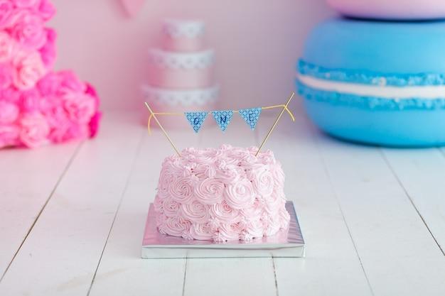 Festlicher rosarose ombre sahnekuchen auf großer blauer makrone. erstes jahr kuchen smash.