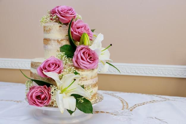 Festlicher rustikaler kuchen mit blumen, rose und lilie.