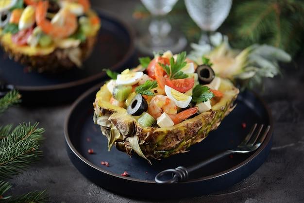 Festlicher salat aus garnelen, kiwi, oliven, weichkäse, wachteleiern, kirschtomaten in ananastellern.