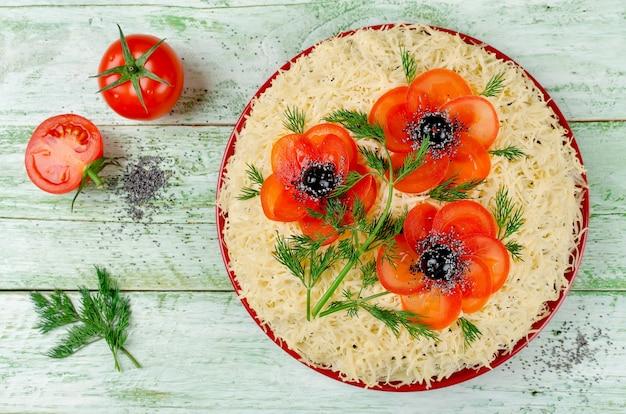 Festlicher salat mit geriebenem käse bestreut und mit mohnblumen aus geschnittenen tomaten und oliven dekoriert. kunst-essen