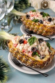 Festlicher salat mit huhn in der hälfte der ananas auf hellblauem hintergrund, neujahr, valentinstag, romantisches abendessen, nahaufnahme, vertikale ausrichtung