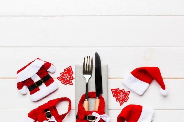Festlicher satz der gabel und des messers auf hölzerner, draufsicht von dekorationen des neuen jahres und sankt-kleidung und hut, weihnachtskonzept