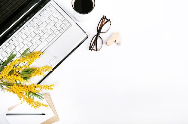Festlicher satz des frühlinges mit blumen und ein laptop auf einem weißen hintergrund
