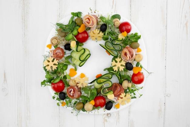 Festlicher snack mit gemüse, speck, käse und mikrogrün.