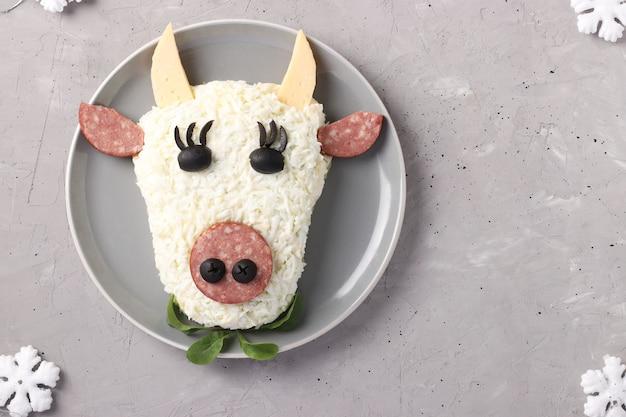 Festlicher stierförmiger salat auf hellgrauem hintergrund, symbolisches essen für neues jahr, draufsicht, horizontales format, raum für text