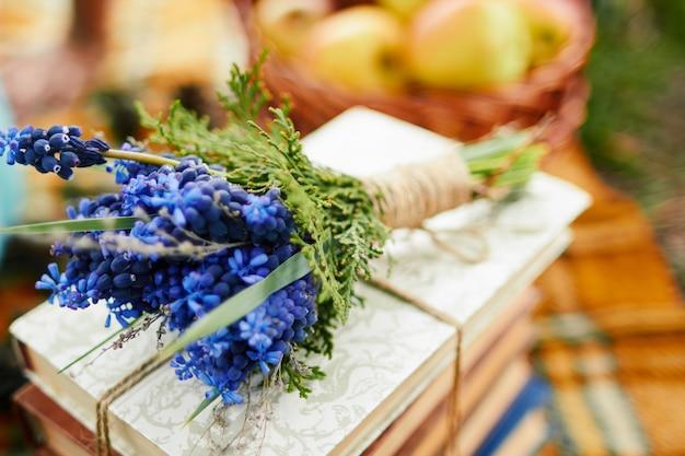 Festlicher strauß wilder blauer blumen auf bücherstapel