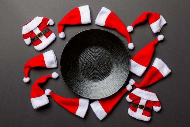Festlicher tellersatz verziert mit weihnachtsmann-hut auf buntem hintergrund. draufsicht weihnachtsessen konzept.