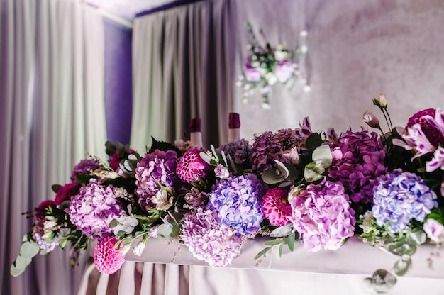 Festlicher tisch dekoriert mit komposition aus violetten, lila, rosa blumen und grün im bankettsaal. tisch-jungvermählten in der umgebung auf hochzeitsfeier.
