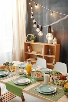 Festlicher tisch für thanksgiving oder weihnachtsfeier mit hängenden lampen