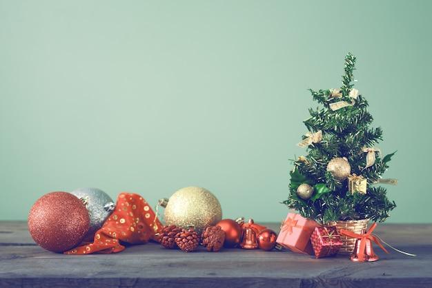 Festlicher weihnachtsbaum steht auf dunklen brettern.