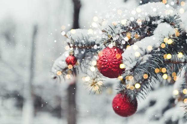 Festlicher weihnachtsbaum verziert mit roten spielzeugglaskugeln mit goldenen höhepunkten. winterlandschaft mit schnee und weihnachtsbäumen.