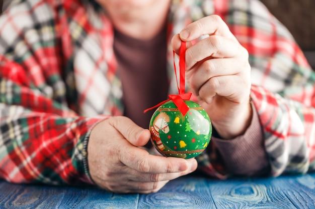 Festlicher weihnachtsdekorationsball in der männlichen hand