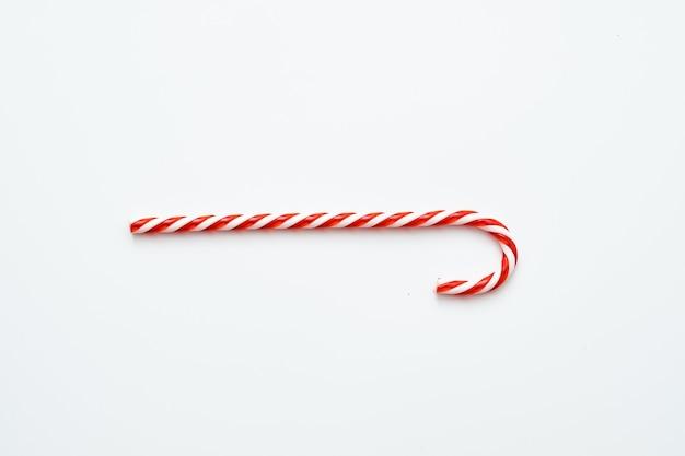 Festlicher weihnachtsgenuss. flache lage der gestreiften roten zuckerstange lokalisiert auf weiß