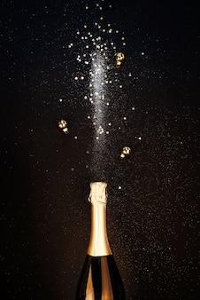 Festlicher weihnachtshintergrund. flasche champagner mit funkeln und weihnachtsschmuck. frohes neues jahr-konzept.