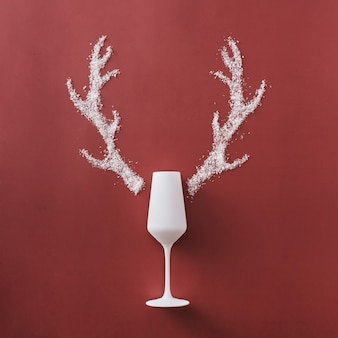 Festlicher weihnachtshintergrund mit elegantem weißem champagner-champagner und geweih aus winterschnee über einem quadratischen roten hintergrund mit exemplar für einen saisonalen gruß