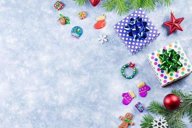 Festlicher weihnachtshintergrund mit tannenzweigen, weihnachtssymbolen, geschenkboxen, bunten dekorationen, kopienraum. ansicht von oben