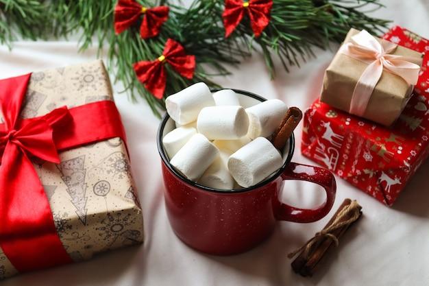Festlicher weihnachtshintergrund mit weihnachtsbaum, rote tasse mit marshmallows, geschenken, zimtstangen